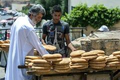 Un hombre examina una carretilla cargada con el pan plano que es vendido adyacente al cuadrado de Lahdim en Meknes en Marruecos Fotografía de archivo libre de regalías