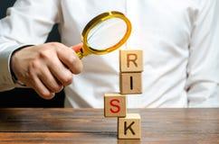 Un hombre explora una torre de cubos con el riesgo de la palabra B?squeda y correcci?n de errores y de fracasos Gesti?n de riesgo imagen de archivo libre de regalías