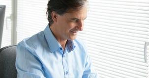 Un hombre feliz de escritura en el ordenador portátil almacen de metraje de vídeo