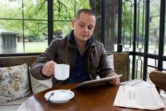 Un hombre feliz que lee un ebook en una cafetería Foto de archivo libre de regalías