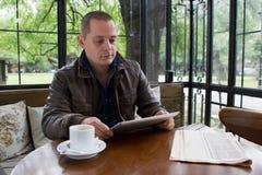 Un hombre feliz que lee un ebook en una cafetería Fotos de archivo