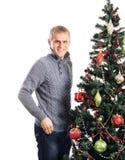 Un hombre feliz que se coloca cerca del árbol de navidad Fotos de archivo