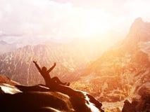 Un hombre feliz que se sienta en una montaña en la puesta del sol Imagen de archivo