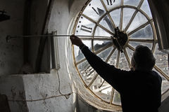 Un hombre fija un reloj en la iglesia Imagen de archivo