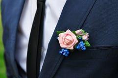 Un hombre fino joven en un traje clásico con un lazo y una camisa blanca y una rosa en su ojal fotos de archivo