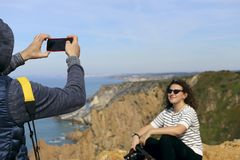 Un hombre fotografía a una muchacha con una cámara en el teléfono imagen de archivo libre de regalías
