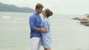 Un hombre frota ligeramente a una muchacha por el pelo, la abraza y besa Un par de amantes se basa sobre el mar metrajes