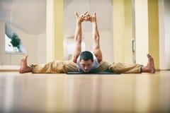 Un hombre fuerte joven que hace yoga ejercita - actitud del ángulo recto de Samakonasana en el estudio de la yoga Imagen de archivo