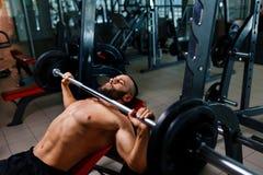 Un hombre fuerte que resuelve ejercicios con un barbell en un fondo del gimnasio Un individuo atlético mantiene la placa del barb Fotografía de archivo