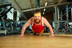 Un hombre gordo divertido con una barba en el gimnasio foto de archivo libre de regalías