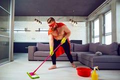 Un hombre gordo, divertido en un traje del super héroe está limpiando la casa imagen de archivo