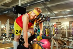 Un hombre gordo está cansado en un simulador en el gimnasio Imágenes de archivo libres de regalías