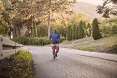 Un hombre gordo joven, al aire libre naturaleza, corriendo en la carretera de asfalto foto de archivo