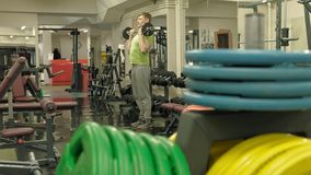 Un hombre gordo levanta un barbell del ez mientras que se coloca en el gimnasio Ejercicio para el b?ceps Aptitud Forma de vida sa almacen de metraje de vídeo
