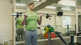 Un hombre gordo levanta un barbell del ez mientras que se coloca en el gimnasio Ejercicio para el b?ceps Aptitud Forma de vida sa metrajes