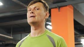 Un hombre gordo levanta un barbell del ez mientras que se coloca en el gimnasio Ejercicio para el b?ceps Aptitud Forma de vida sa almacen de video