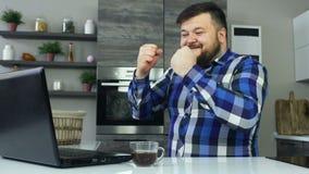 Un hombre gordo se sienta en la cocina delante de un ordenador portátil, disfruta y bebe el café Un varón grueso está en la cocin almacen de metraje de vídeo