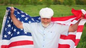 Un hombre gris-barbudo con la bandera de los Estados Unidos celebra Día de la Independencia el 4 de julio almacen de metraje de vídeo