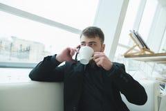 Un hombre habla por el teléfono y bebe el café en un café cerca de la ventana Platos de un hombre de negocios en un café Foto de archivo libre de regalías