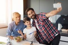 Un hombre hace el selfie en un smartphone blanco con su hijo y padre mayor Fotos de archivo