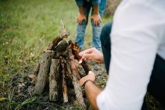 Un hombre hace un fuego en el bosque por la tarde del verano imágenes de archivo libres de regalías