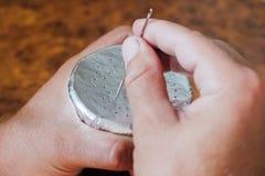 Un hombre hace los agujeros con una aguja en una hoja de la cachimba Preparación de un cuenco para la cachimba que fuma fotografía de archivo libre de regalías
