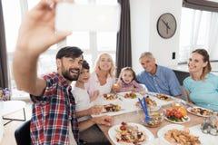 Un hombre hace un selfie en un smartphone blanco con su familia Celebran día de la acción de gracias Fotos de archivo