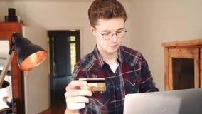 Un hombre hace una compra en línea con una tarjeta de crédito metrajes