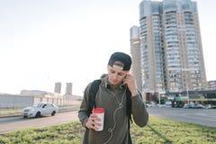 Un hombre hermoso con un vidrio de la bebida caliente en sus manos escucha la música y corrige los auriculares en sus oídos contr Imágenes de archivo libres de regalías