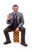 Un hombre hermoso en un traje y vidrios, con ajedrez y un tubo para Fotos de archivo libres de regalías