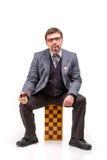 Un hombre hermoso en un traje y vidrios, con ajedrez y un tubo para Imagenes de archivo
