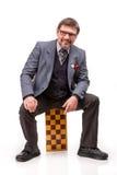 Un hombre hermoso en un traje y vidrios, con ajedrez y un tubo para Foto de archivo libre de regalías