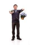Un hombre hermoso en un traje y vidrios, con los dulces y las flores; W Imágenes de archivo libres de regalías