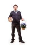 Un hombre hermoso en un traje y vidrios, con los dulces y las flores; W Fotos de archivo libres de regalías
