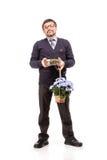 Un hombre hermoso en un traje y vidrios, con los dulces y las flores; W Fotografía de archivo