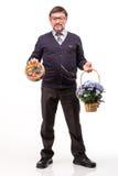 Un hombre hermoso en un traje y vidrios, con los dulces y las flores; W Foto de archivo
