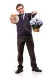 Un hombre hermoso en un traje y vidrios, con los dulces y las flores; W Imagenes de archivo