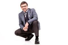 Un hombre hermoso en un traje y vidrios, con un reloj; Backgr blanco Fotografía de archivo libre de regalías