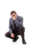 Un hombre hermoso en un traje y vidrios, piensa; Fondo blanco Fotografía de archivo libre de regalías