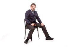 Un hombre hermoso en un traje y vidrios, se sienta, con un tubo para el smok Foto de archivo