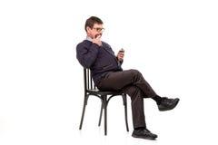 Un hombre hermoso en un traje y vidrios, se sienta, con un tubo para el smok Fotos de archivo