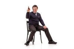 Un hombre hermoso en un traje y vidrios, se sienta, con un tubo para el smok Imágenes de archivo libres de regalías