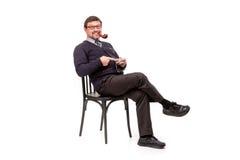 Un hombre hermoso en un traje y vidrios, se sienta, con un tubo para el smok Foto de archivo libre de regalías
