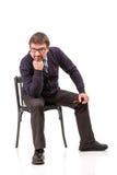 Un hombre hermoso en un traje y vidrios, se sienta, con un tubo para el smok Fotografía de archivo libre de regalías