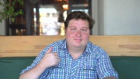 Un hombre hermoso, gordo con el cuerpo grande muestra los pulgares para arriba en el café o el restaurante metrajes