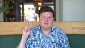Un hombre hermoso, gordo con la victoria grande de las demostraciones del cuerpo firma adentro el café o el restaurante metrajes