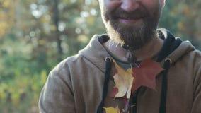 Un hombre hermoso, joven con los vidrios y barba con las hojas de otoño tejidas en ella almacen de metraje de vídeo