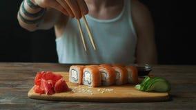 Un hombre hermoso joven está comiendo los rollos de sushi con los palillos en un restaurante japonés metrajes