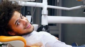 Un hombre hermoso joven que se sienta en una silla de los dentistas, él da vuelta y sonríe en cámara almacen de video
