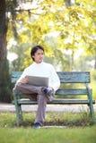 Un hombre hermoso joven que usa el ordenador portátil que se sienta en un ben Fotos de archivo